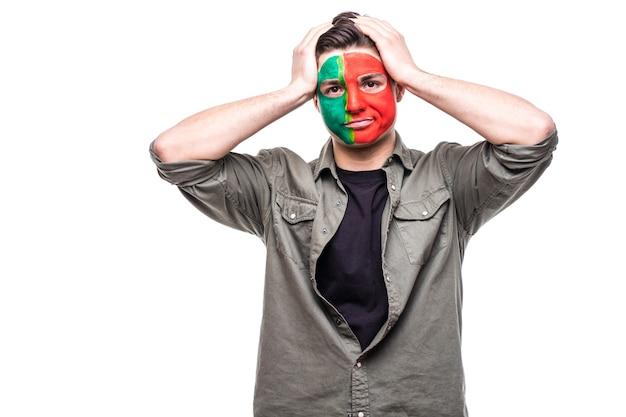 Przystojny mężczyzna, fan kibiców reprezentacji portugalii, pomalowany flagą, dostaje do aparatu nieszczęśliwe smutne sfrustrowane emocje. emocje fanów.