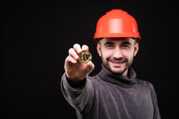 Przystojny mężczyzna górnik w ochronnej hemlet spiczasty bitcoin na czarnym tle