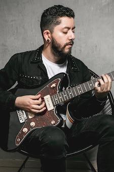 Przystojny mężczyzna gra na gitarze elektrycznej