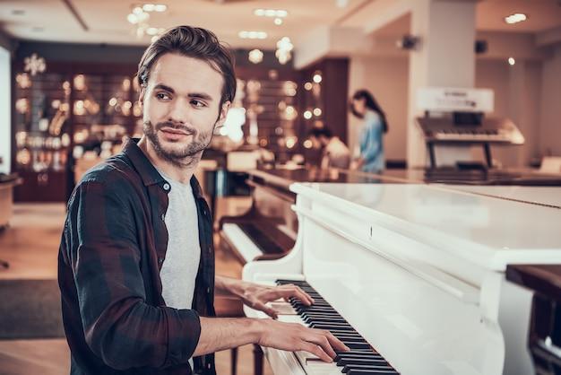 Przystojny mężczyzna gra na pianinie w sklepie instrumentów muzycznych.