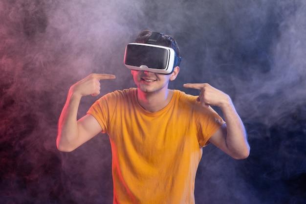 Przystojny mężczyzna gra w wirtualnej rzeczywistości na ciemnej powierzchni