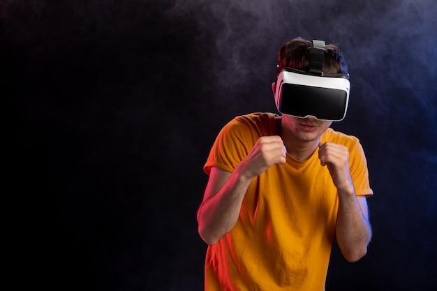 Przystojny mężczyzna grający w grę walki w vr na ciemnej powierzchni