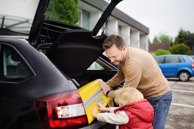 Przystojny mężczyzna i jego mały syn idzie na wakacje, ładując walizkę w bagażniku samochodu