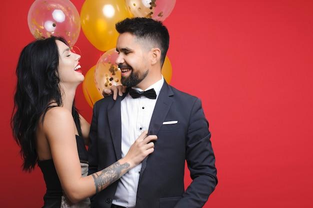 Przystojny mężczyzna i ładna kobieta w eleganckich strojach, trzymając oczy zamknięte i wesoło się śmiejąc, stojąc w pobliżu wiązki balonów na czerwonym tle
