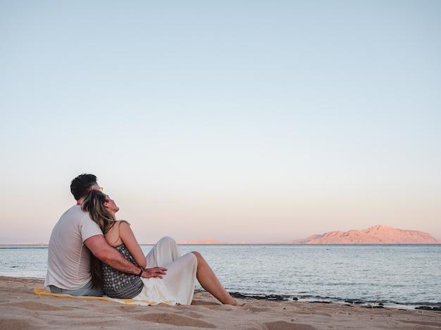 Przystojny mężczyzna i śliczna kobieta siedzi na plaży