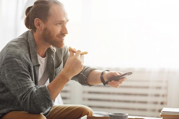 Przystojny mężczyzna je pizzę i ogląda telewizję