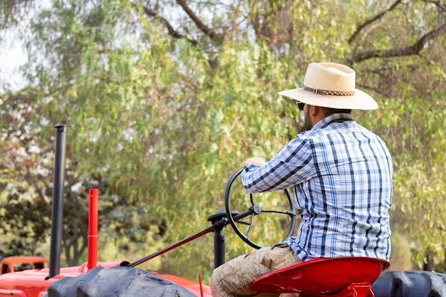 Przystojny mężczyzna jedzie ciągnika pracować w gospodarstwie rolnym z okularami przeciwsłonecznymi