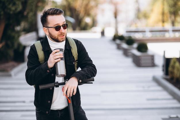 Przystojny mężczyzna jedzie na hulajnodze i pije kawę z termosem