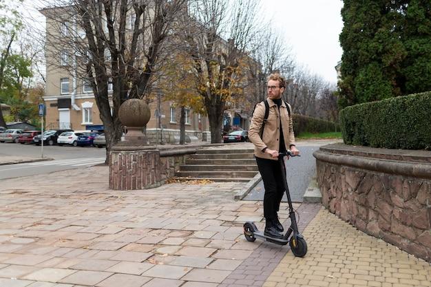 Przystojny mężczyzna jedzie na skuterze elektrycznym