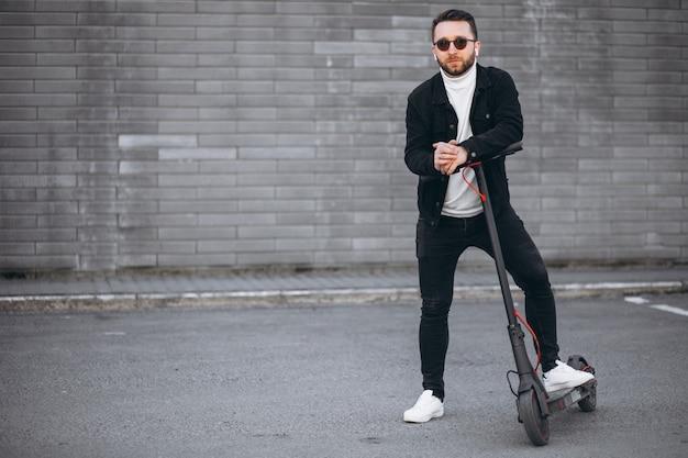 Przystojny mężczyzna jedzie w mieście na hulajnodze