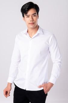Przystojny mężczyzna jest ubranym białą koszula na bielu