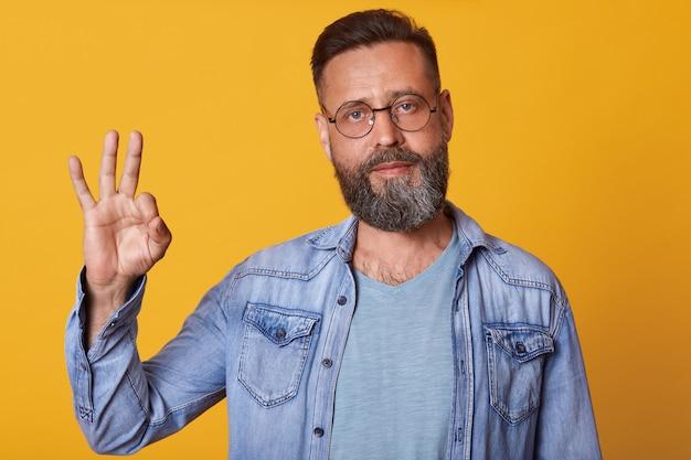 Przystojny mężczyzna jest ubranym drelichową kurtkę i szarą koszulę z brodą stoi przeciw żółtej studio ścianie i pokazuje ok znaka ręką