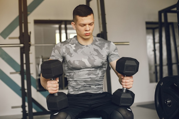 Przystojny mężczyzna jest zaangażowany w siłownię