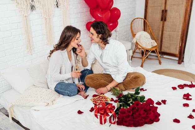 Przystojny mężczyzna karmi dziewczynę czekoladowymi cukierkami i pije szampana siedząc na łóżku i w domu, koncepcja walentynki