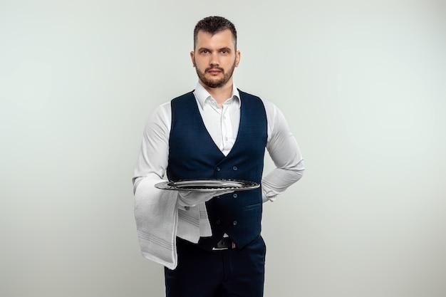 Przystojny mężczyzna kelner, w białej koszuli, trzymając srebrną tacę. koncepcja obsługi personelu obsługującego klientów w restauracji.