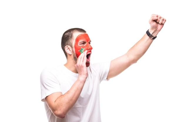 Przystojny mężczyzna kibicem, fanem reprezentacji maroka z malowaną flagą, uzyskuje szczęśliwe zwycięstwo z krzykiem wskazującym ręką. emocje fanów.