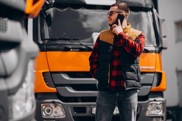Przystojny mężczyzna kierowca ciężarówki stojący przy ciężarówce