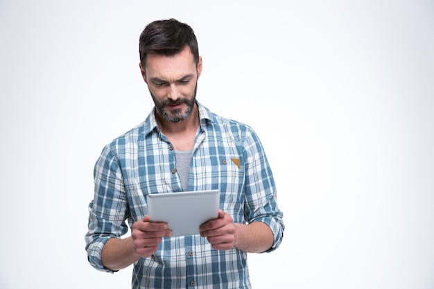 Przystojny mężczyzna korzystający z komputera typu tablet na białym tle na białej ścianie
