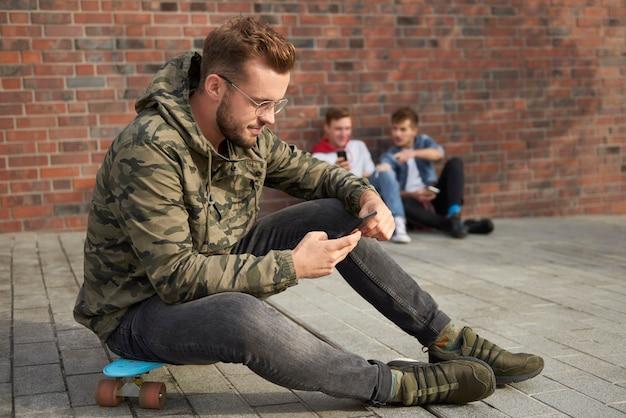 Przystojny mężczyzna korzystający z telefonu komórkowego i siedzący na deskorolce