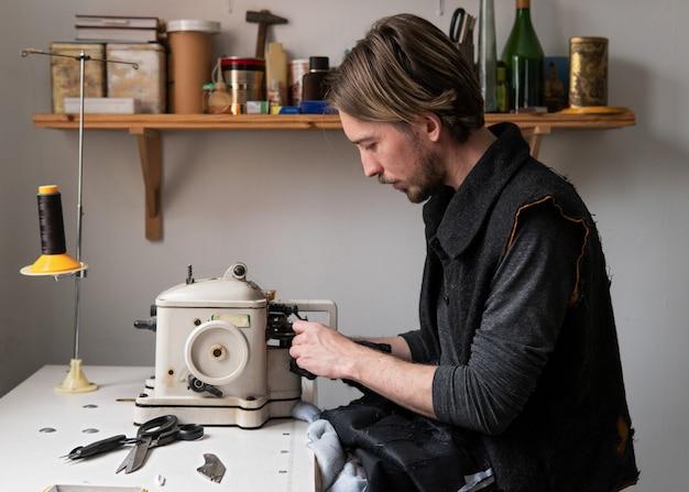Przystojny mężczyzna krawczyna szy futro na kuśnierzy maszynie w warsztacie