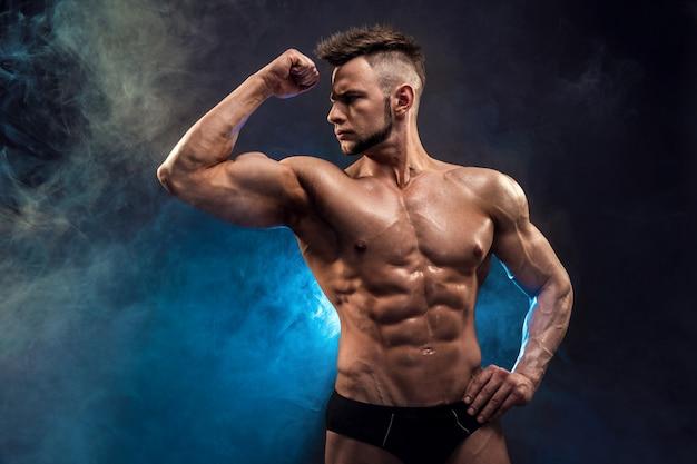 Przystojny mężczyzna kulturysta kulturysta. mokre fitness muskularne ciało na ciemnym tle dymu.