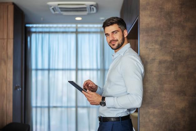 Przystojny mężczyzna, ładnie ubrany, oparty plecami o ścianę, trzyma w rękach cyfrowy tablet i uśmiecha się