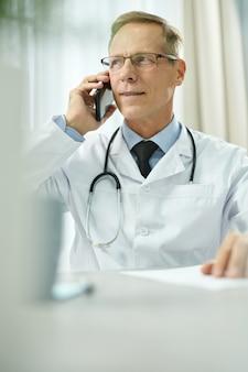 Przystojny mężczyzna lekarz rozmawia przez telefon komórkowy w klinice