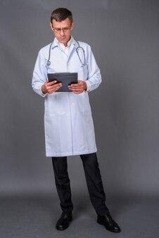 Przystojny mężczyzna lekarz z krótkimi włosami na szarym tle