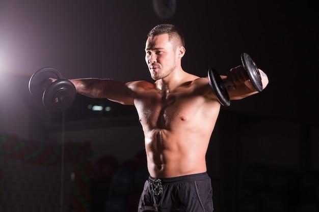 Przystojny mężczyzna lekkoatletyczny moc z hantle. silny kulturysta z sześciopakiem, doskonałymi mięśniami brzucha i ramion