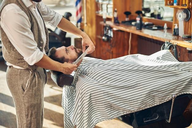 Przystojny mężczyzna leżący na krześle fryzjerskim z przystrzyżoną brodą