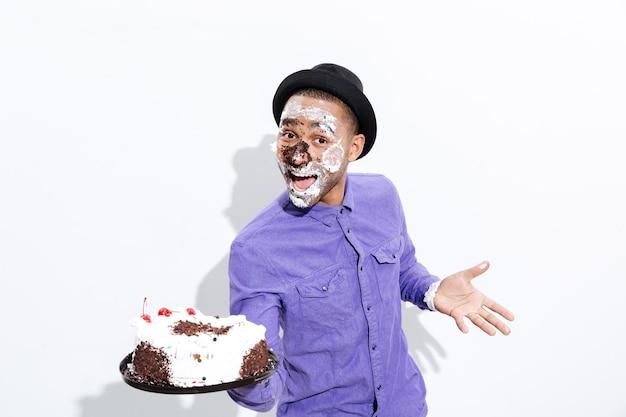 Przystojny mężczyzna ma ciasto na całej twarzy na białym tle