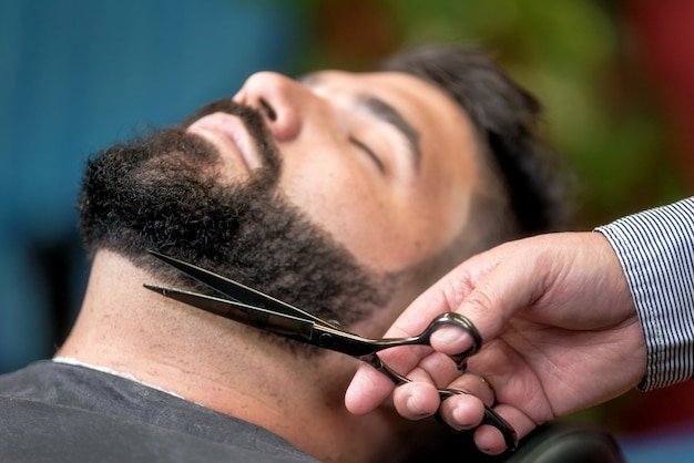 Przystojny mężczyzna ma golenie z nożycami przy zakładem fryzjerskim.