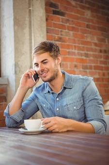 Przystojny mężczyzna ma kawę i dzwonić