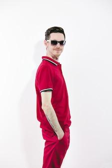 Przystojny mężczyzna ma na sobie okulary przeciwsłoneczne i ubrania marsala