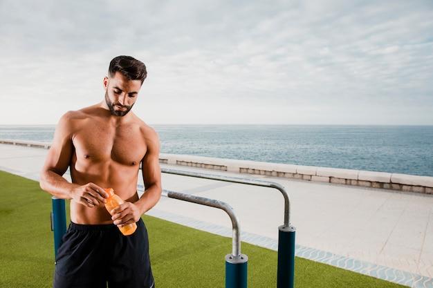 Przystojny mężczyzna ma przerwę i nawadnia podczas treningu