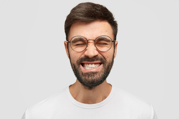 Przystojny mężczyzna marszczy brwi i kleci zębami, ma zamknięte oczy, stara się na czymś skoncentrować, nosi luźną koszulkę