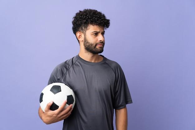 Przystojny mężczyzna młody piłkarz marokański na białym tle na fioletowy patrząc z boku