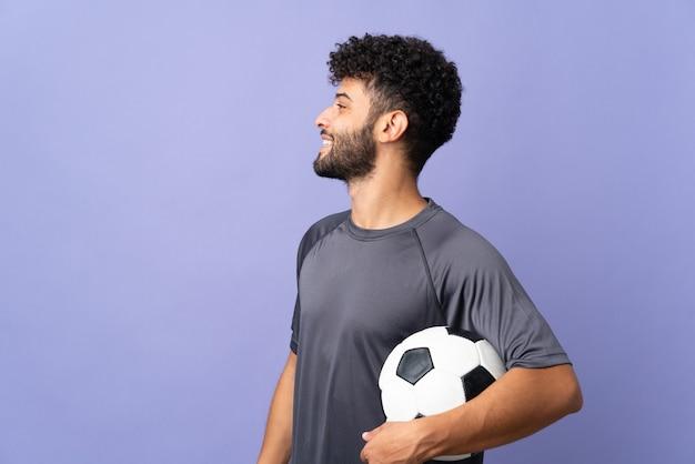 Przystojny mężczyzna młody piłkarz marokański na białym tle na fioletowy śmiech w pozycji bocznej