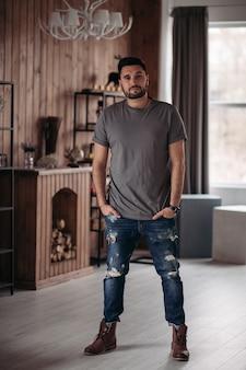 Przystojny mężczyzna model pozuje do kamery w luksusowych apartamentach z rękami w kieszeniach