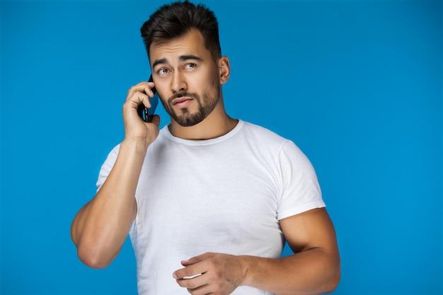 Przystojny mężczyzna mówi przez telefon i wydaje się zagubiony