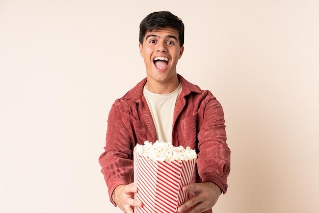 Przystojny mężczyzna na białym tle gospodarstwa duże wiadro popcorns