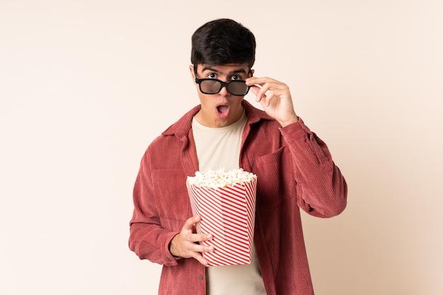 Przystojny mężczyzna na białym tle zaskoczony okularami 3d i gospodarstwa duże wiadro popcorns