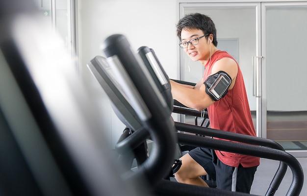 Przystojny mężczyzna na działającej maszynie w gym, sprawność fizyczna pokój