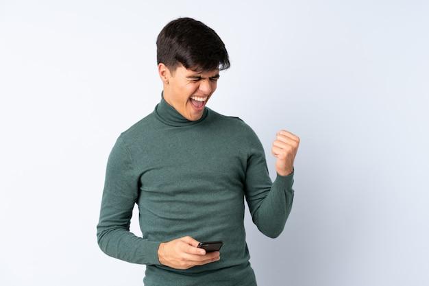 Przystojny mężczyzna na niebieską ścianą z telefonem w pozycji zwycięstwa