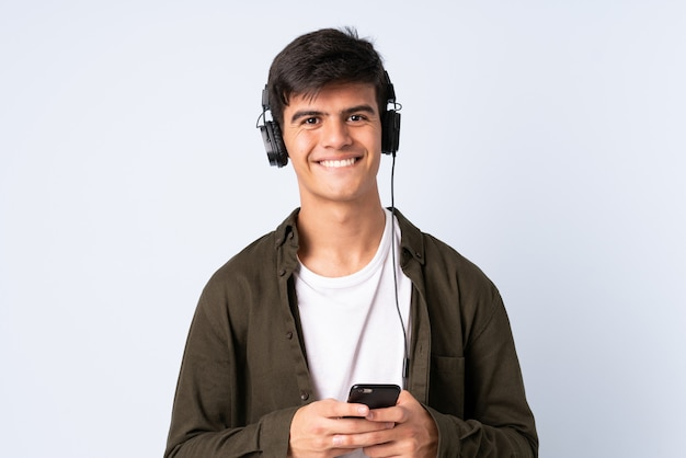 Przystojny mężczyzna na pojedyncze niebieskim tle słuchania muzyki z telefonu komórkowego i patrząc z przodu