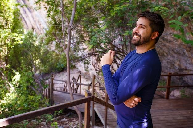 Przystojny mężczyzna na szlak wakacje uśmiechający się patrząc na kamery. mężczyzna uśmiechający się w parku. mężczyzna krzyż ramiona
