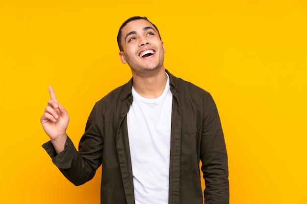 Przystojny mężczyzna na żółtym myślący pomysł, wskazując palcem w górę