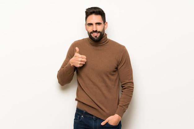 Przystojny mężczyzna nad biel ścianą dawać aprobaty gestowi z rękami i ono uśmiecha się