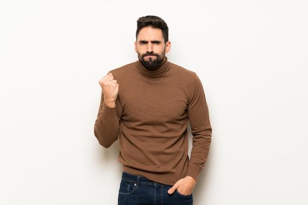 Przystojny mężczyzna nad biel ścianą z gniewnym gestem