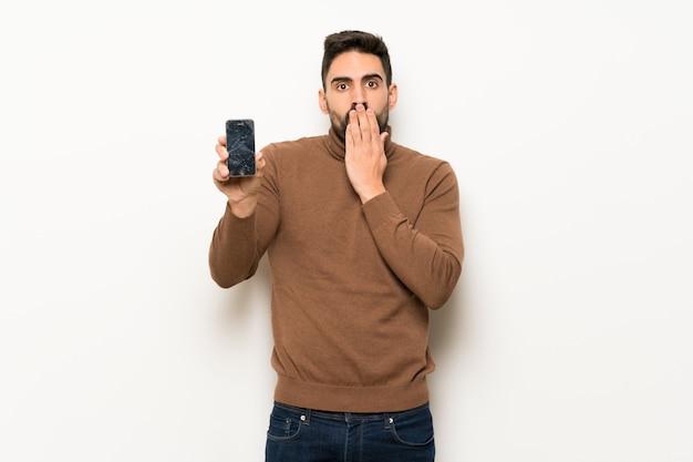 Przystojny mężczyzna nad biel ścianą z skołatanym mienia łamającym smartphone